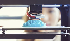 a 3D printer using a layer-by-layer deposition process to print a three-dimensional object while a young woman looks on in the background