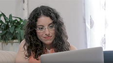 a female college student looking at the screen of her silver-cased laptop computer