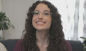 smiling young adult with long, dark, curly hair wearing glasses