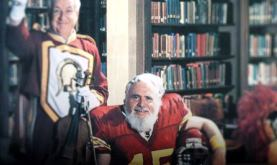 photo of Solomon Golomb in a football uniform sitting in a library with another male adult standing to his left