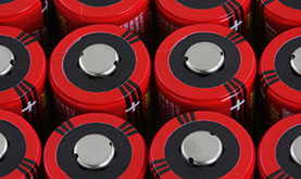 three rows of bright red lithium batteries tightly packed with anode side up