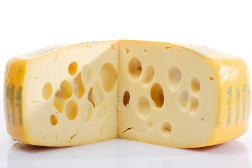 a circular block of Swiss cheese with a wedge cut out so the holes are visible