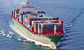 green-hulled cargo ship carrying a large, colorful load of pallets