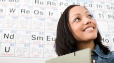 young woman in front of periodic table