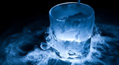 Dry ice sublimating from a drinking glass which is backlit, atop a glass table. Blue light gives the image an eerie look as carbon dioxide vapor rises from the cup.