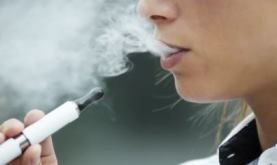 image of a young woman exhaling aerosols from an e-cig
