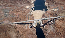 aerial photo of a bridge spanning the Colorado River at the site of the Hoover Dam