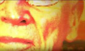 pixellated, close-up rendering of a part of an older man's face in yellow, orange, and red