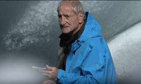 an older man wearing a blue jacket close to a white glacier