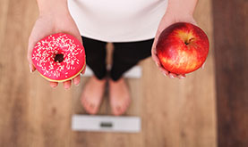 close-up of a donut and apple in a woman's hands as she weighs herself on a bathroom scale
