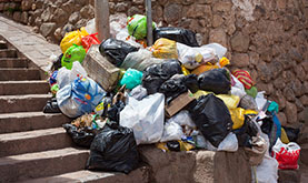 outdoor photo showing a huge pile of trash, mainly plastic bags, on a stone stairway