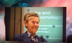 photo of Helen Quinn in front of a slide presentation with a backdrop of the cosmos behind it
