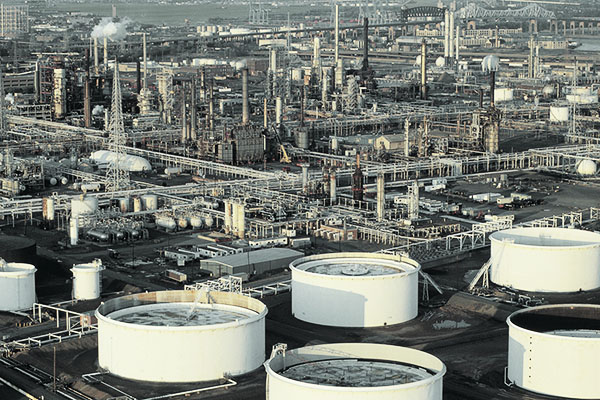 oil refinery and storage tanks within a sprawling cityscape