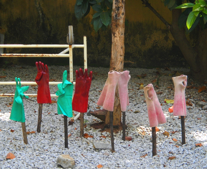 Red-, pink-, and green-colored rubber gloves propped up on sticks in order to dry