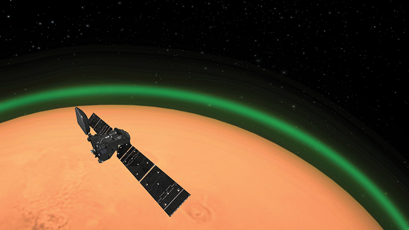 starry background with red Mars in the middle ground and to lower left with green ring above the surface representing airglow, and TGO spacecraft in foreground