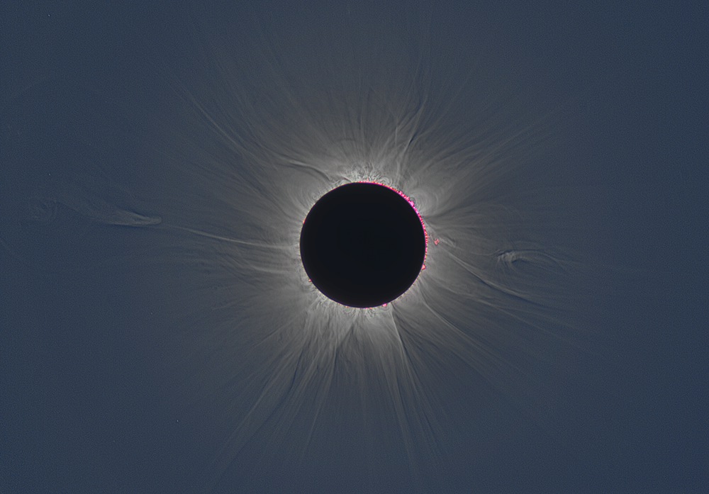 A black disk surrounded by some pink beads, with rays of light emanating in all directions against a dark blue sky