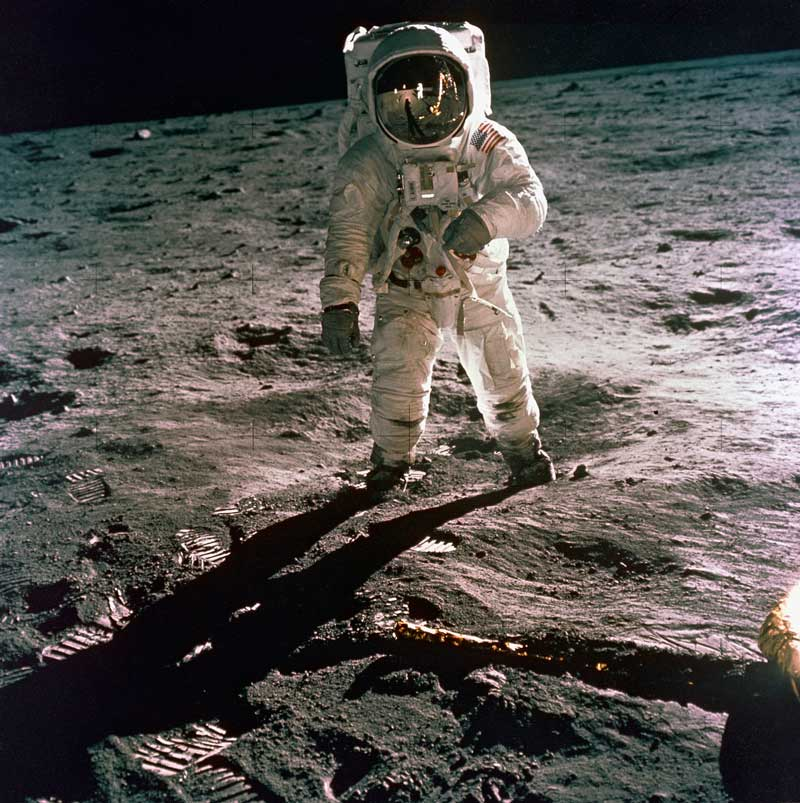 Buzz Aldrin in a spacesuit on the Moon, with the black of space in the sky and the rugged, gray, lunar landscape in the background and foreground