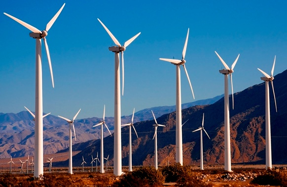 A group of wind turbines; brown mountains and blue sky are in the background