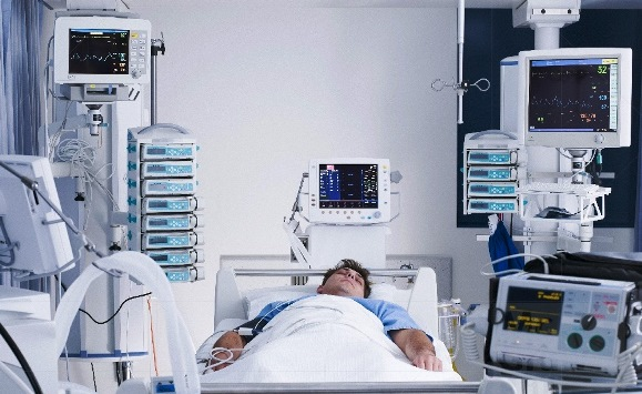 Full-length view (photo) of a male patient in a hospital bed, with many medical devices surrounding him