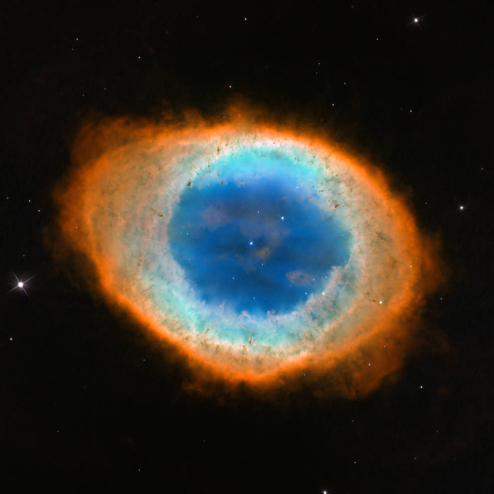 The Ring Nebula, which id oval-shaped and in optical light has a blue core surrounded by light yellow and orange shells, with a bright white dwarf at its center
